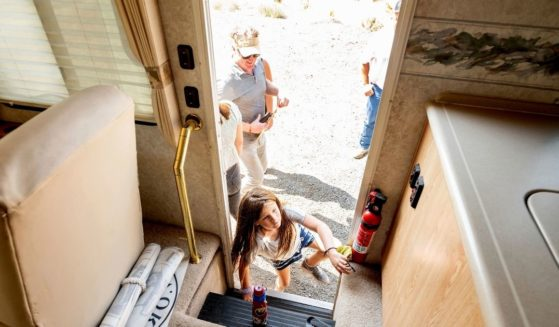 Luna Faircloth boards a donated RV while delivering it to a Dixie Fire victim on Sept. 5, 2021, in Sierra County, Calif. Behind her is dad Woody Faircloth, who runs the non-profit EmergencyRV.org.