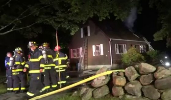 Firefighters survey the scene where a woman was saved from a fire by her neighbor.