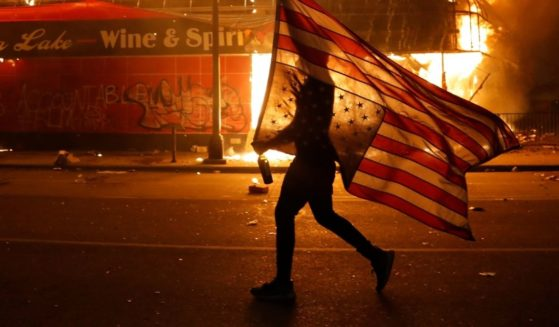 A Minneapolis protester carries a U.S. flag past a burning building on May 28, 2020, during protests over the death of George Floyd.