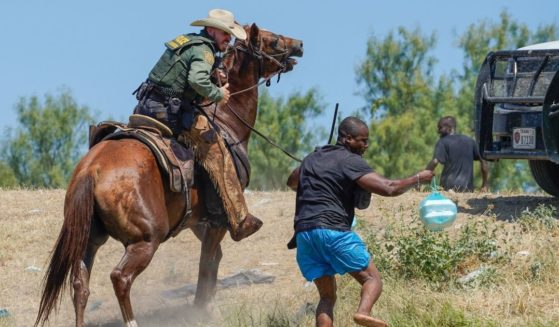 A United States Border Patrol agent on horseback uses the reins to try and stop a Haitian migrant from entering an encampment on the banks of the Rio Grande near the Acuna Del Rio International Bridge in Del Rio, Texas, on Sept. 19, 2021.