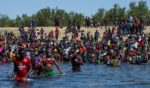 Haitian migrants, part of a group of over 10,000 people staying in an encampment on the US side of the border, cross the Rio Grande river to get food and water in Mexico, after another crossing point was closed near the Acuna Del Rio International Bridge in Del Rio, Texas on Sept. 19, 2021.