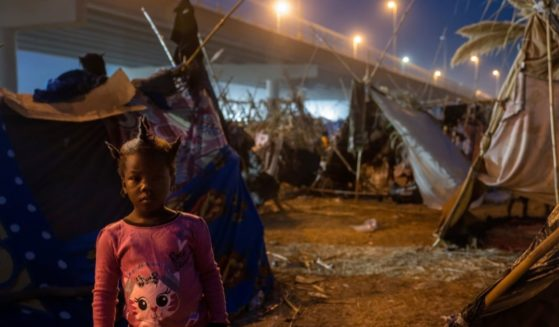 A Haitian girl stands at a migrant camp at the U.S.-Mexico border on Tuesday in Del Rio, Texas.