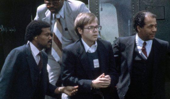 U.S. Marshals escort John Hinckley Jr. as he returns to a marine base via helicopter in Quantico, Virginia on Aug. 8, 1981.