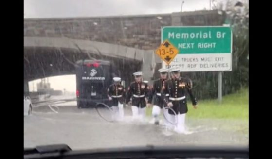 Marines in dress blues walk through floodwaters to help a stranded motorist.
