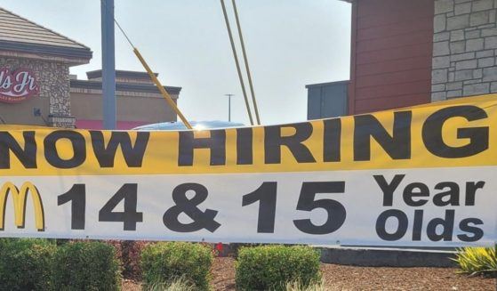 A banner outside a McDonald's advertises job openings available to 14- and 15-year-olds.