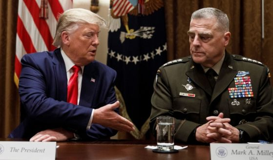 President Donald Trump extends a hand to Chairman of the Joint Chiefs of Staff Gen. Mark Milley, as he speaks to media during a briefing with senior military leaders in the Cabinet Room at the White House in Washington, D.C., on Oct. 7, 2019.