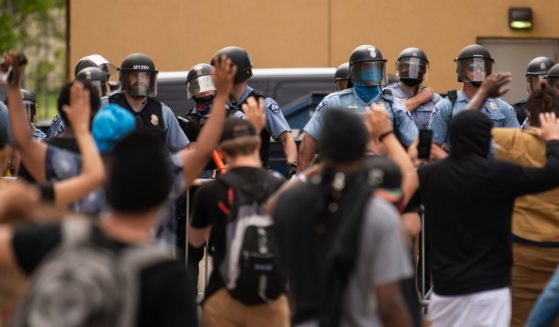 Police officers stand in a line while facing demonstrators outside the 3rd Police Precinct in Minneapolis on May 27, 2020.
