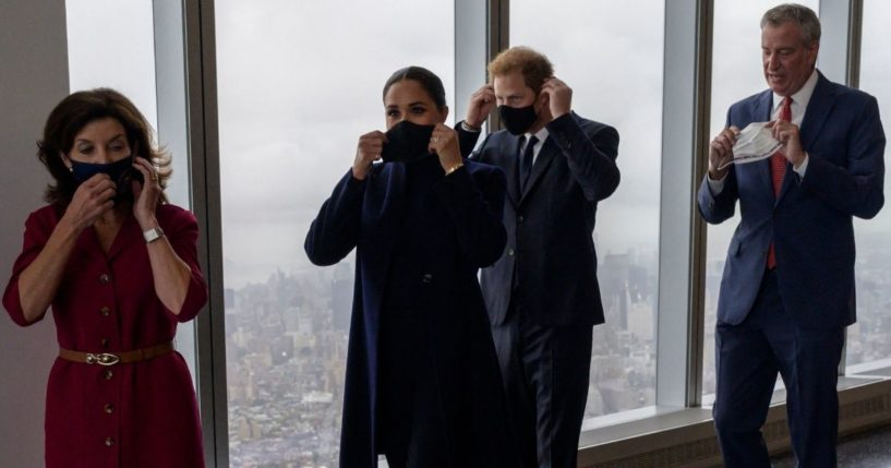 Britain's Prince Harry, center, and Meghan Markle walk with New York Gov. Kathy Hochul, left, and New York City Mayor Bill de Blasio and remove their masks for a photo op during a visit to the One World Trade Center observation deck in New York on Thursday.