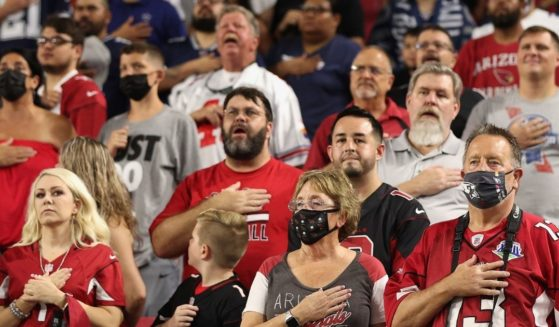 Fans stand for the national anthem before the NFL preseason game between the Arizona Cardinals and the Dallas Cowboys at State Farm Stadium on Aug. 13, 2021, in Glendale, Arizona.