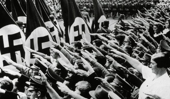 Crowds give the fascist salute while Nazi Labor Corps march past them, bearing flags with swastikas, during an annual congress for the National Socialist Party in Nuremberg, Germany.