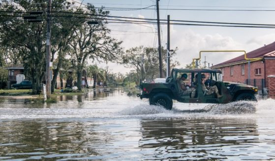 Members of the National Guard drive through floodwater on Wednesday in Jean Lafitte, Louisiana.