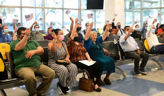 New U.S. citizens wave flags at the conclusion of a naturalization ceremony ahead of World Refugee Day by U.S. Citizenship and Immigration Services on June 17, 2021, in Los Angeles.
