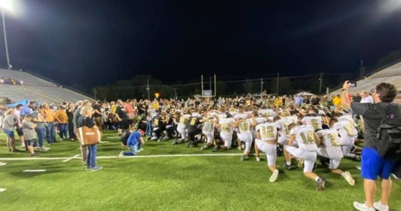 Upperman and Stone Memorial high school football players lead fans in prayer on the field after their game Friday night in Tennessee.