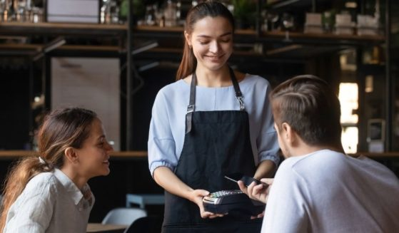 A restaurant server is pictured with a couple at a table in the stock image above.