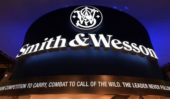 """A sign at the Smith & Wesson booth is shown in this file photo from a 2016 trade show. Firearms manufacturer Smith & Wesson announced Thursday that it is moving its headquarters due to a """"changing business climate for firearms manufacturing in Massachusetts."""" The company will relocate to Tennessee."""