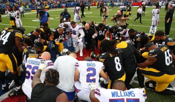 Players for the NFL's Pittsburgh Steelers and Buffalo Bills kneel and pray before their Sunday game.