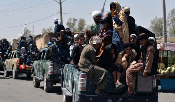 Taliban fighters atop vehicles parade along a road to celebrate after the U.S. pulled all its troops out of Afghanistan in Kandahar on Wednesday.