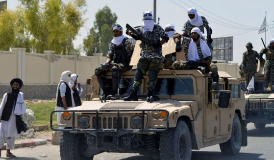 Taliban fighters atop Humvee vehicles parade along a road to celebrate after the U.S. pulled all its troops out of Afghanistan, in Kandahar on Wednesday following the Taliban's military takeover of the country.