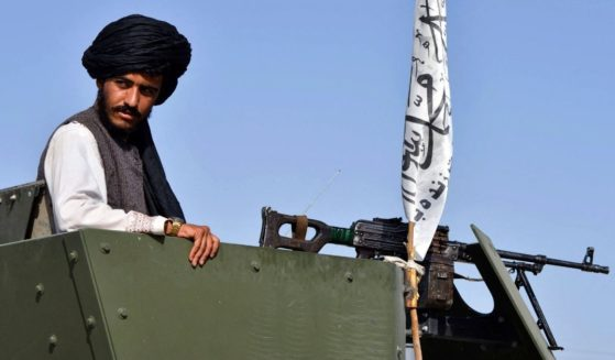 A Taliban fighter rides on an armored vehicle during a parade to celebrate the withdrawal of U.S. troops from Afghanistan on Wednesday in Kandahar.
