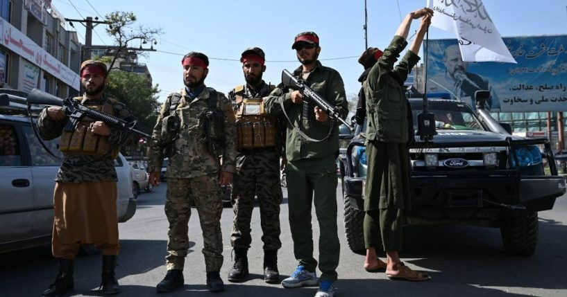 Taliban fighters stand guard along a road in Kabul on Thursday.