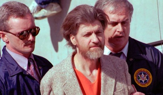 Theodore John Kaczynski, nicknamed the Unabomber, is flanked by federal agents as he is led to a car from the federal courthouse in Helena, Montana, on April 4, 1996.