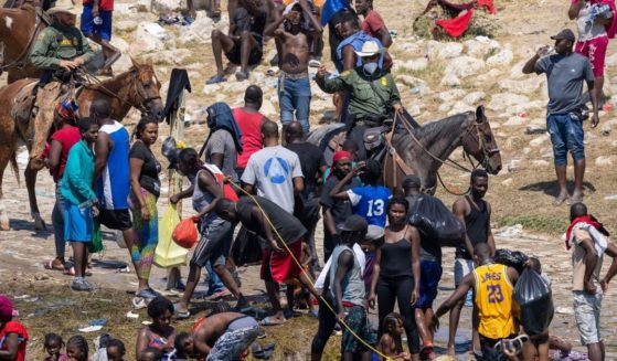 Border Patrol agents are seen among a group of Haitian migrants at the Rio Grande River in Del Rio, Texas, on Monday.