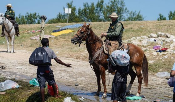 U.S. Border Patrol agents are seen interacting with Haitian migrants at the banks of the Rio Grande in Del Rio, Texas, on Sunday.