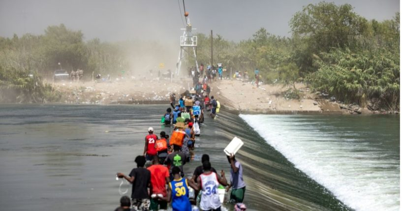 A group of migrants are seen walking toward the international bridge in Del Rio, Texas, on Saturday.