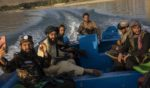 Taliban fighters are seen sitting in a boat at the Qargha dam on the outskirts of Kabul, Afghanistan, on Friday.