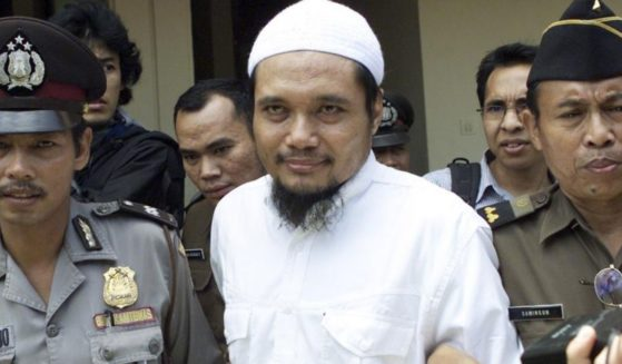 Abu Rusdan is seen being escorted by security in Jakarta, Indonesia, on Nov. 3, 2003.
