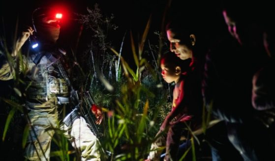 A member of the Texas National Guard addresses an immigrant family seeking asylum as they arrive on U.S. soil after crossing the Rio Grande on June 19, 2021, in Roma, Texas. That type of scene is playing out again this month in the Lone Star State.