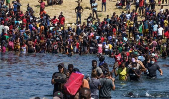 Some of a group of over 10,000 migrants from Haitian and other countries migrants are seen crossing the Rio Grande on Sunday.