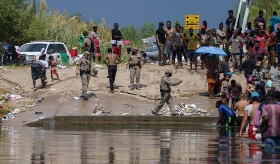 Texas state troopers deal with a large group of illegal immigrants, many from Haiti, along the Rio Grande next near the Del Rio-Acuna Port of Entry in Del Rio, Texas, on Saturday.