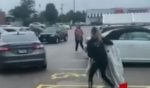 A suspect carrying an armload of clothing attempts to catch up to a car that sped away as a store security guard approached.