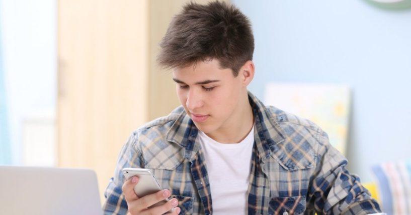 A teenage boy looks at his phone.