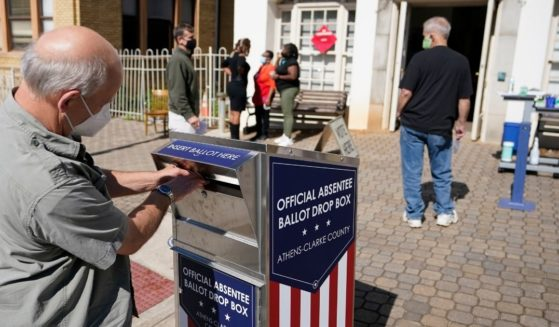 A voter turns in a ballot during early voting in Oct. 19, 2020, file photo from Athens, Georgia, in the Peach State's Athens-Clarke County.