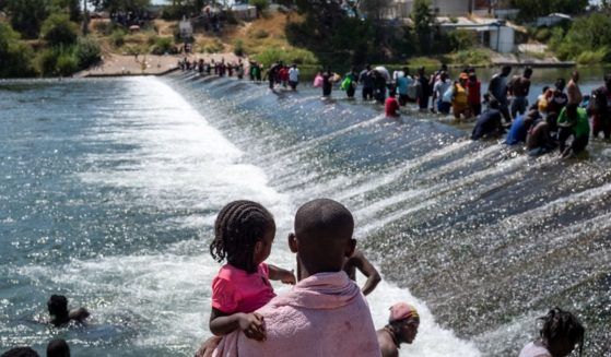 An illegal immigration from Haiti holds his daughter as others cross the Rio Grande.