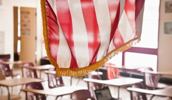 A stock photo shows the American flag hanging in a classroom at a school.