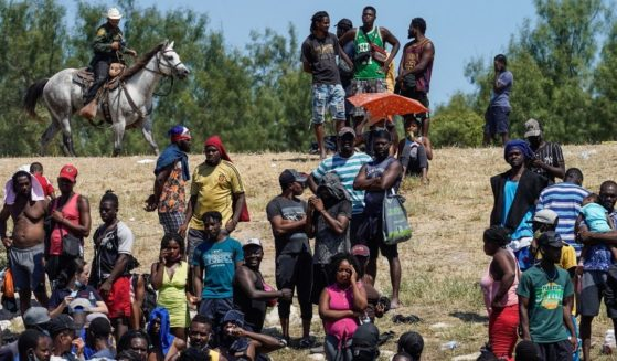 US Border Patrol Agents are seen on horseback near Haitian migrants at the banks of the Rio Grande River in Del Rio, Texas, on Sept. 19.