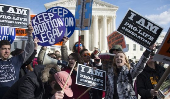 Pro-abortion and pro-life activists are seen outside the Supreme Court in Washington, D.C., on Jan. 22, 2015.