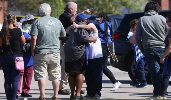 People are seen standing with police at the scene of a shooting at a Kroger's grocery store in Collierville, Tennessee, on Thursday.