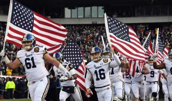 Players of the Navy Midshipmen of the U.S. Naval Academy arrive waving the American flag prior to the annual Army-Navy football game at Lincoln Financial Field in Philadelphia on Dec. 8, 2018.