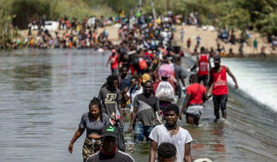 Migrants cross the Rio Grande from Mexico into the U.S. near a migrant camp under the international bridge in Del Rio, Texas, on Sept. 18.