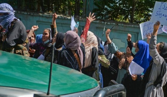 Afghan women shout slogans next to a Taliban fighter during an anti-Pakistan demonstration near the Pakistan embassy in Kabul on Sept. 7, 2021.