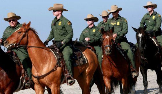 Border Patrol agents ride horses along the beach at Borderfield State Park in San Ysidro, California, on Tuesday, Nov. 20, 2018.