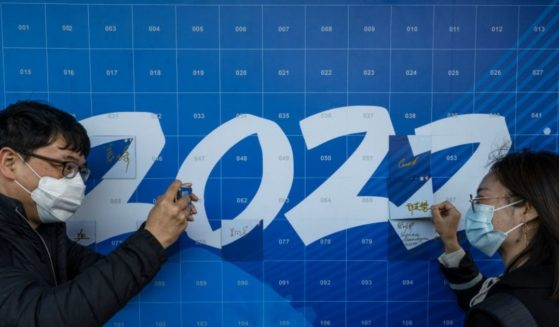A man takes a photo of a woman as she signs a '2022' poster at an event held by the organizing committee of the Beijing 2022 Winter Olympics and Paralympics for international media at their headquarters at Shougang on April 12, in Beijing.