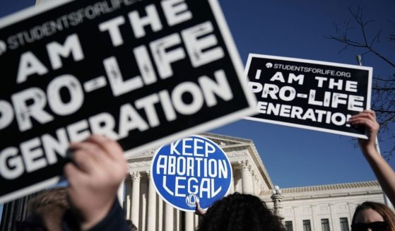 Pro-life activists try to block the sign of a pro-choice activist during the 2018 March for Life on Jan. 19, 2018, in Washington, D.C.