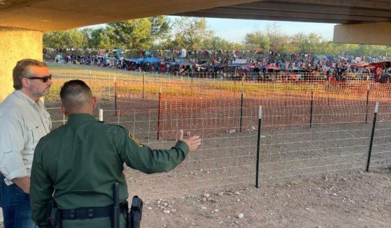 Texas Republican Sen. Ted Cruz speaks with a Border Patrol agent near a bridge in Del Rio, Texas, on Friday.