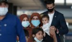 Refugees walk through the departure terminal to a bus at Dulles International Airport after being evacuated from Kabul following the Taliban takeover of Afghanistan on Aug. 31, in Dulles, Virginia.