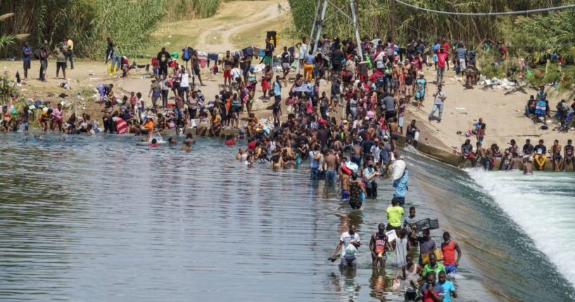 Migrants, many of them Haitian, cross the Rio Grande to get food and supplies near the Del Rio-Acuna Port of Entry in Ciudad Acuna, Coahuila state, Mexico on Saturday.